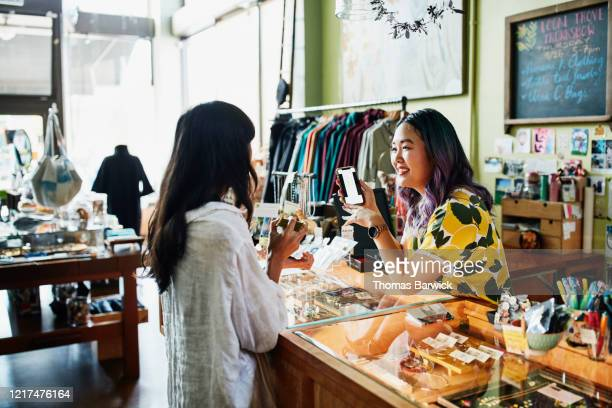 smiling shopkeeper helping client at counter in boutique - small business stock pictures, royalty-free photos & images