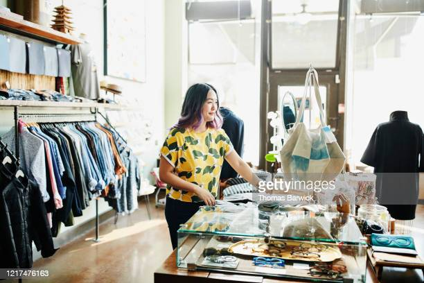 smiling shopkeeper organizing display in boutique - women wearing see through clothing stock pictures, royalty-free photos & images