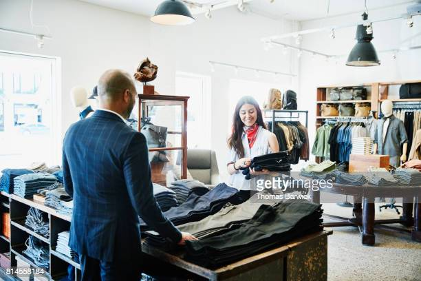 Smiling shopkeeper showing customer a selection of denim in mens clothing boutique