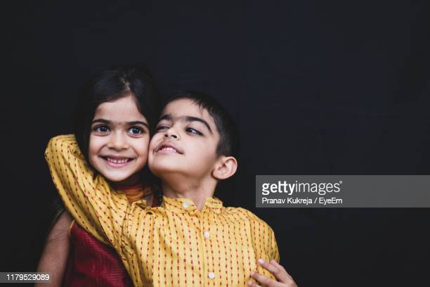 smiling siblings against black background - primary age child stock pictures, royalty-free photos & images