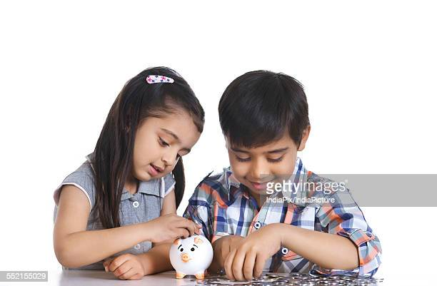 Smiling siblings counting Indian coins while sitting over white background