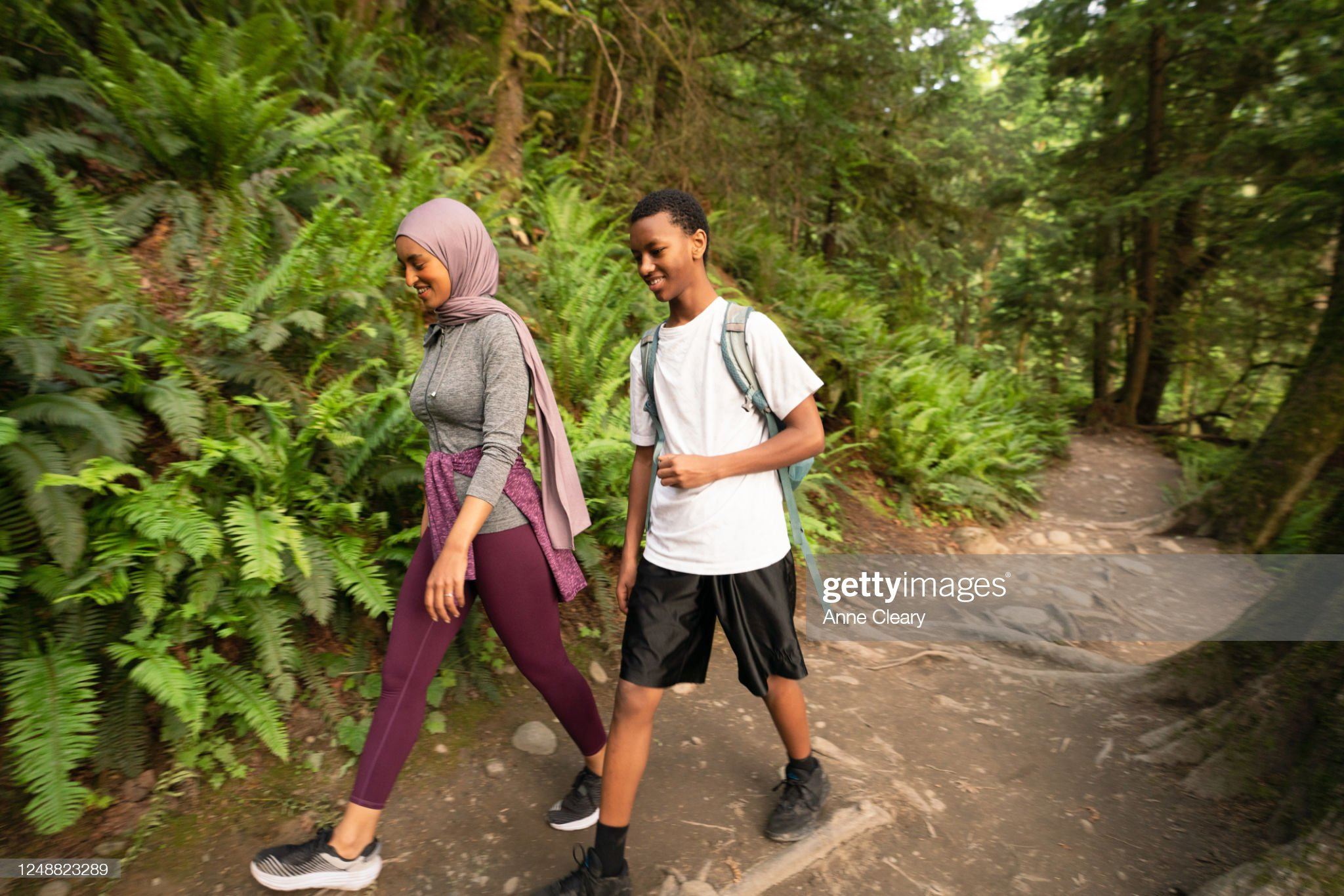 Smiling siblings hiking on trail in forest : Stock Photo