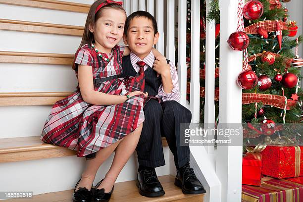 Smiling silbing christmas portrait on staircase
