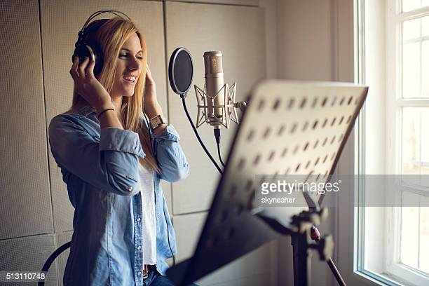 smiling singer recording in music studio. - sound recording equipment stock pictures, royalty-free photos & images