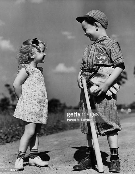 smiling sister and brother in baseball uniform looking at each other - {{relatedsearchurl(carousel.phrase)}} ストックフォトと画像
