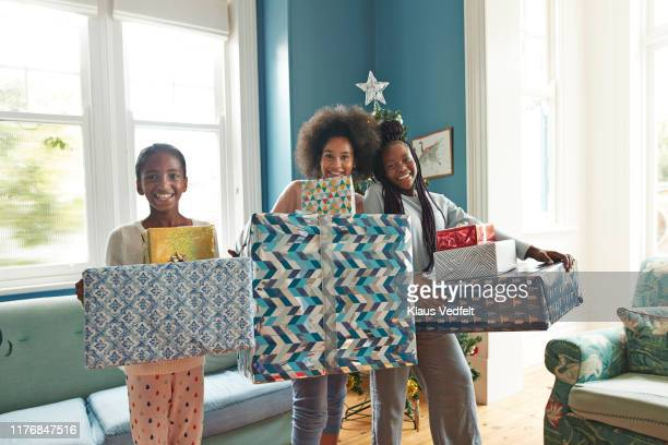 Smiling sisters carrying Christmas gifts at home