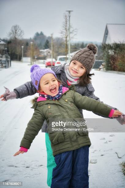 smiling sisters with arms outstretched standing on snow - bayern stock pictures, royalty-free photos & images