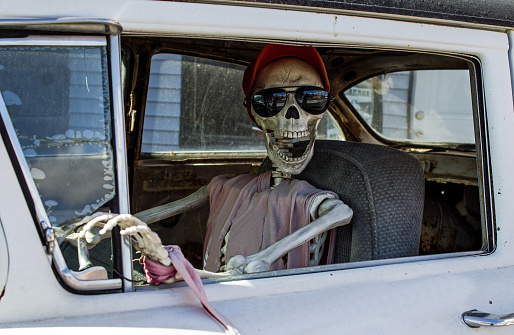 Smiling Skeleton in Sunglasses and a Red Baseball Cap Driving a Car 911541222