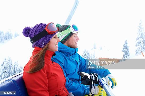 Smiling skiers riding ski lift