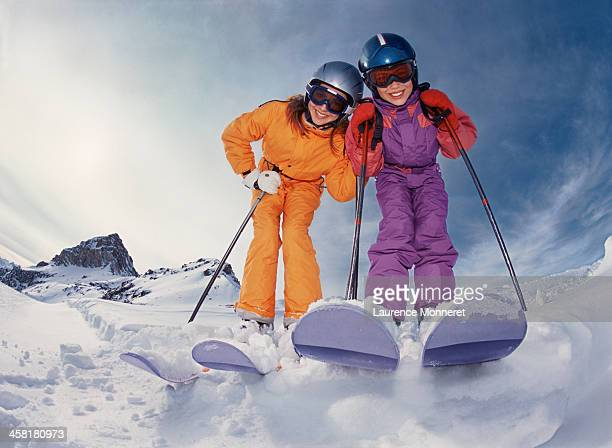 Smiling skiing kids posing with helmets