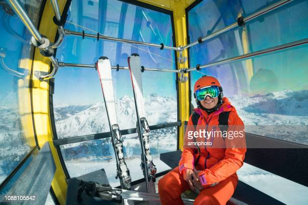 smiling skiing woman going up with cable car in winter mountains - ski lift stock pictures, royalty-free photos & images