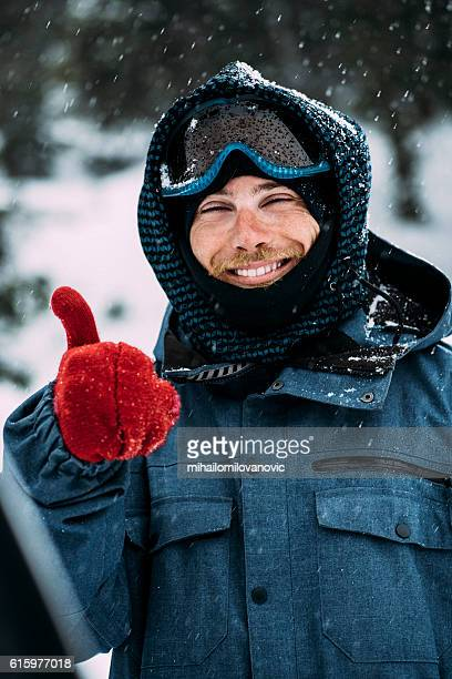 Smiling snowboarder posing