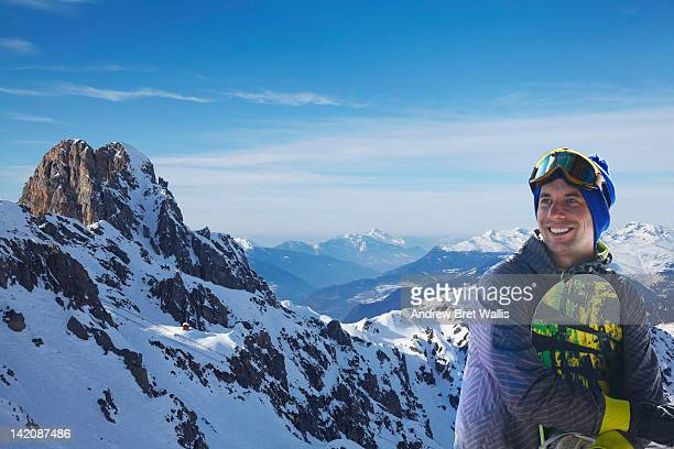 Smiling snowboarder stands at the mountain top