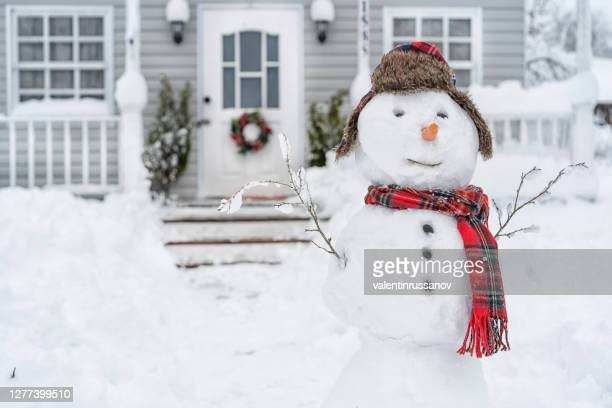 smiling snowman in front of the house on winter day - winter stock pictures, royalty-free photos & images