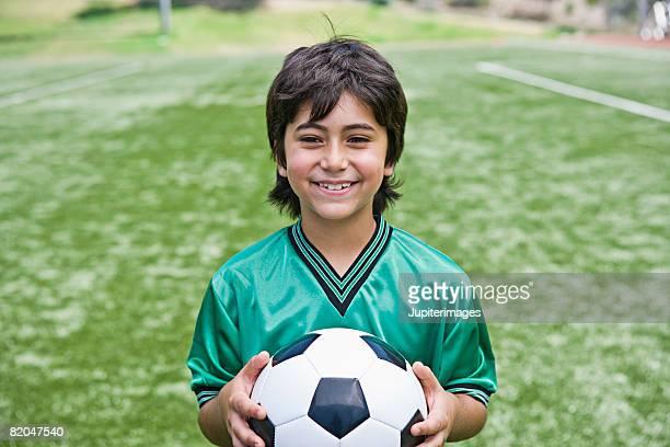 Smiling soccer player boy holding ball