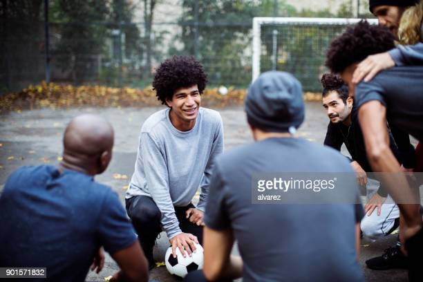 smiling soccer player planning strategy with team - team captain stock pictures, royalty-free photos & images