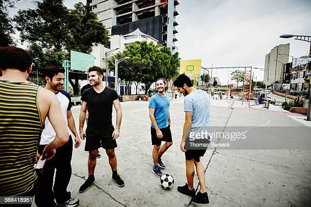 smiling soccer players standing on outdoor court - friendly match stock-fotos und bilder