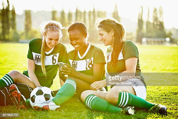 Smiling soccer teammates looking at smartphone