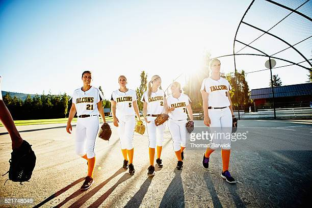Smiling softball players walking off field