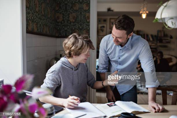 smiling son thanking father for his help in doing homework at home - jeunes garçons photos et images de collection