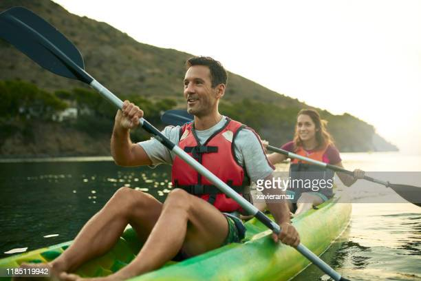 smiling spanish kayakers enjoying paddling at dawn - estilo de vida ativo imagens e fotografias de stock
