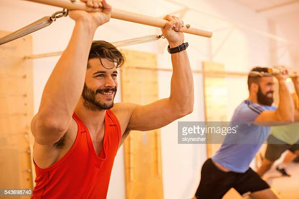 Smiling sportsman doing stretching exercise on Pilates machine.