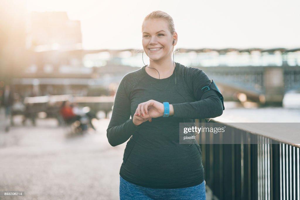 Sonriente la deportista comprobar su reloj inteligente : Foto de stock