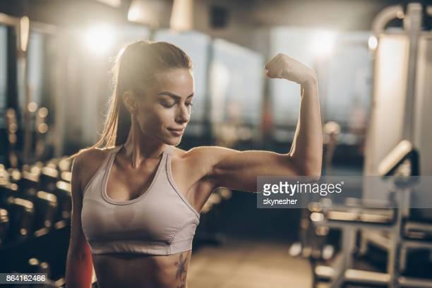 lächelnde sportlerin ihre muskeln im fitnessstudio. - muskel stock-fotos und bilder