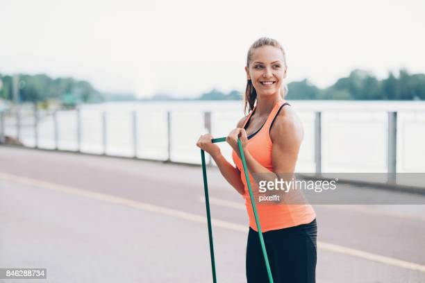 Smiling sportswoman with resistance band