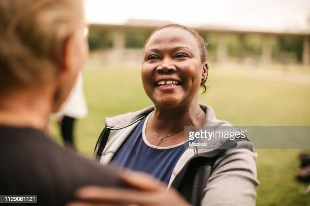 smiling sporty woman talking with senior male friend in park - hand on shoulder stock pictures, royalty-free photos & images