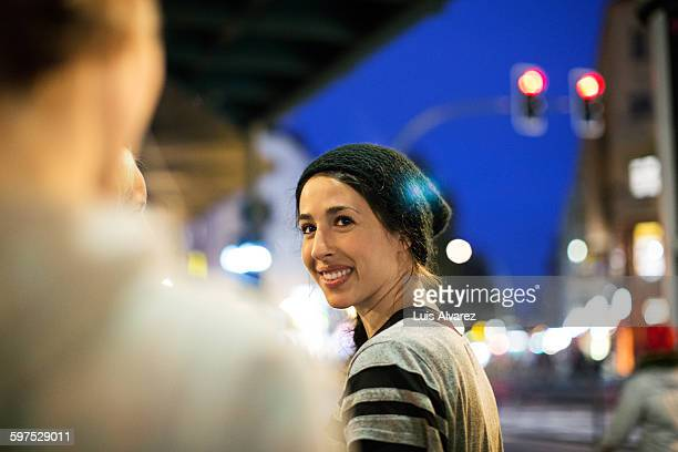 smiling sporty woman with friends in city - mid adult women stock pictures, royalty-free photos & images