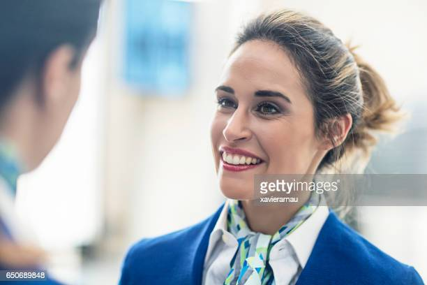 Smiling stewardess looking at coworker in airport