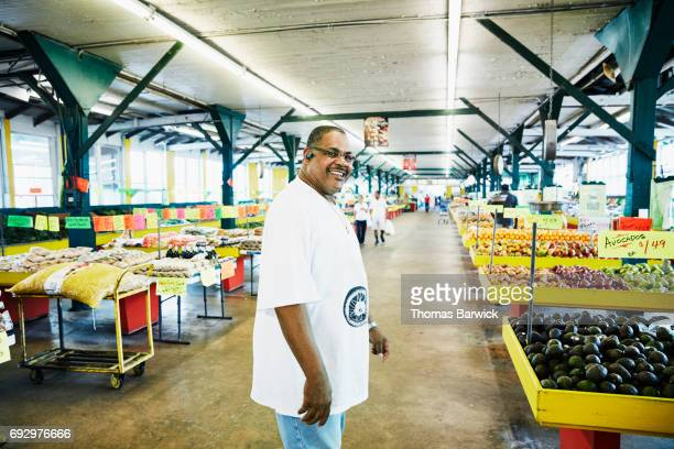 Smiling store manager walking the aisles of produce market