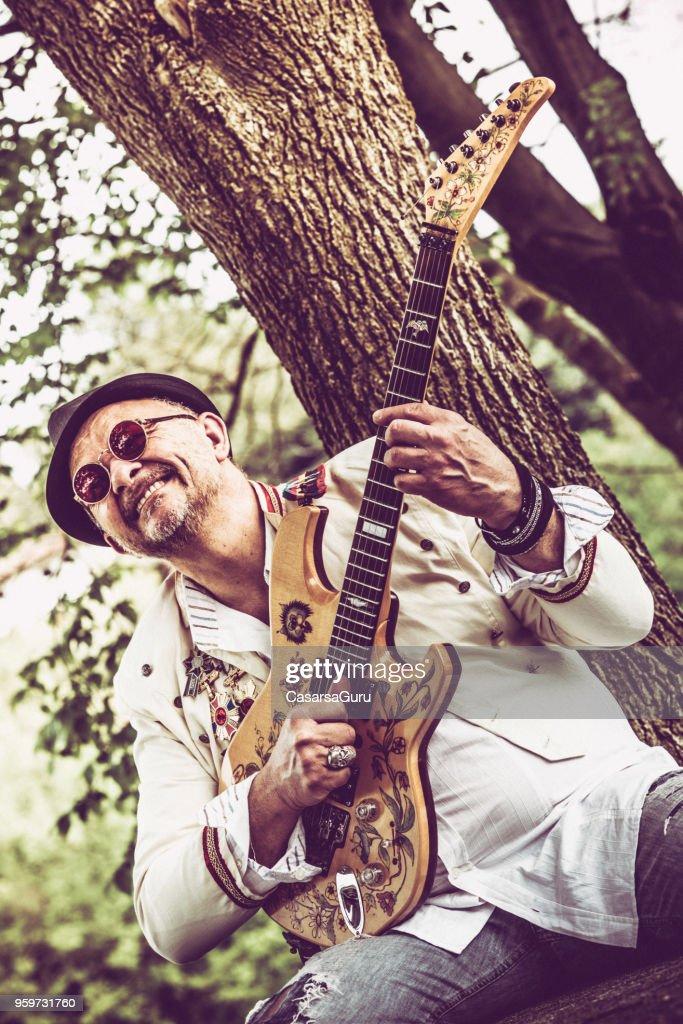 Lächelnd Streetart-Künstler spielt e-Gitarre im öffentlichen Park : Stock-Foto