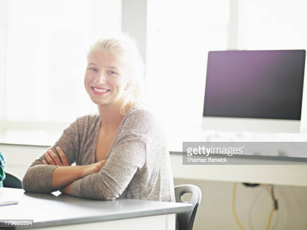 Smiling student at desk in science classroom