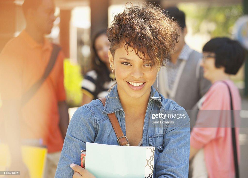 Sorridente aluno carregar pasta : Foto de stock