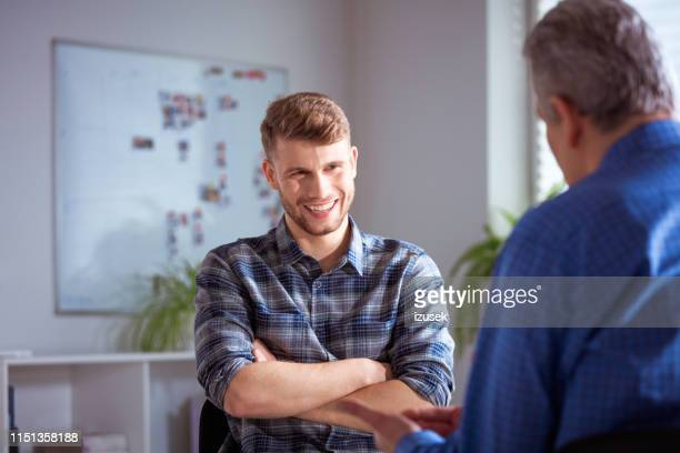 smiling student discussing with male therapist - psychotherapy stock pictures, royalty-free photos & images