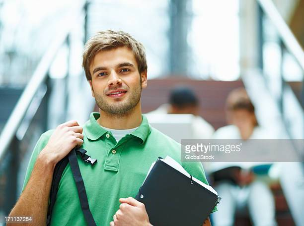 Smiling student holding books with students blurred behind