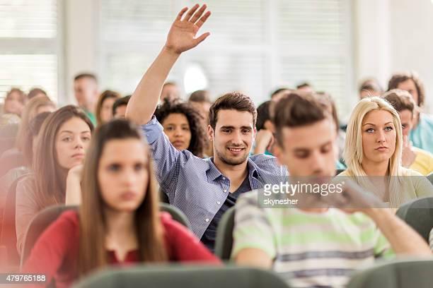Souriant étudiant placer votre disposition pour répondre à la question de salle de conférence.