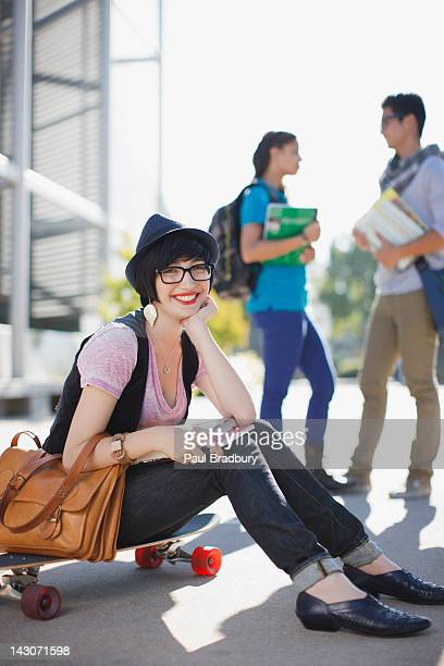 Smiling student sitting on skateboard