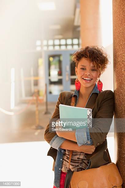 Smiling student standing in school hallway