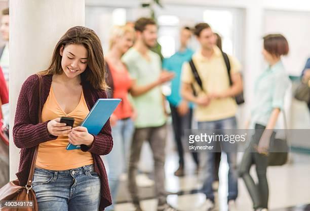 Estudante sorridente mensagens de texto no telefone celular na universidade dos balcões.