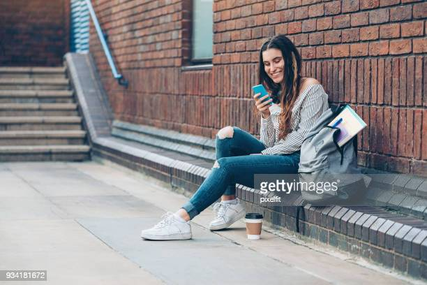 smiling student texting outdoors - college application stock photos and pictures