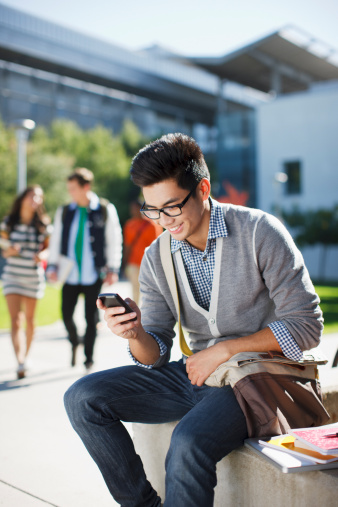 Smiling student using cell phone outdoors - gettyimageskorea