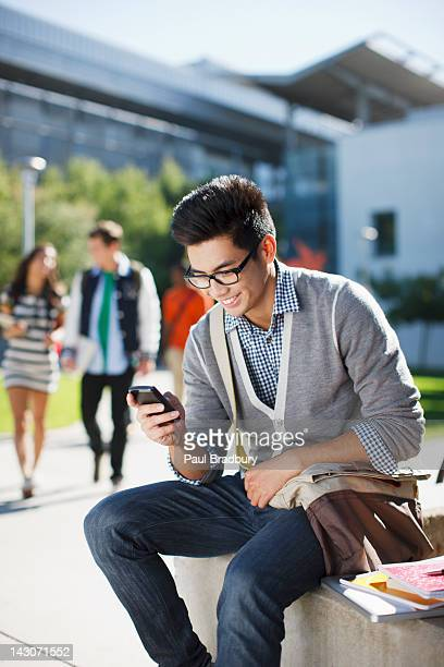 Smiling student using cell phone outdoors