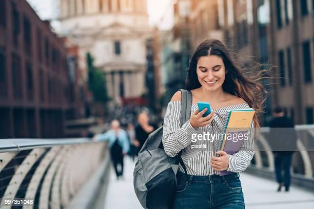 Lächelnd Schüler zu Fuß und SMS