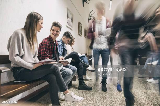 Lachende studenten communiceren terwijl u ontspant in de lobby van een school.
