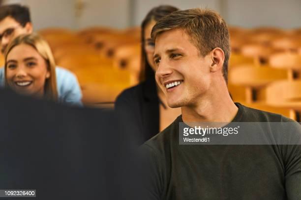 smiling students in auditorium at university - auditorium photos et images de collection