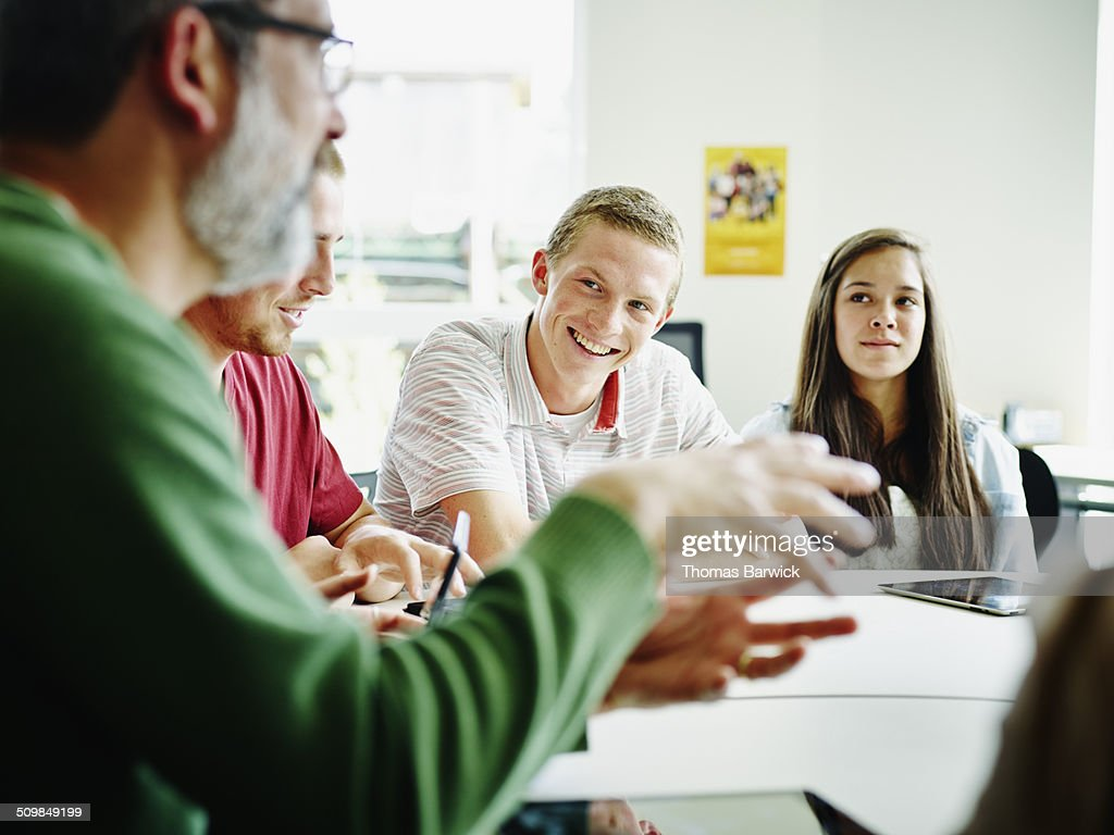 Smiling students listening to teacher lecture : Stock Photo