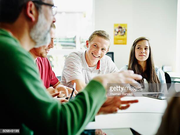 smiling students listening to teacher lecture - enseigner photos et images de collection